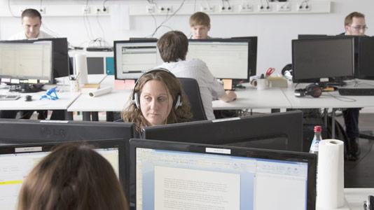 Mitarbeiter von Airmotion Media an Schreibtischen mit Bildschirmen