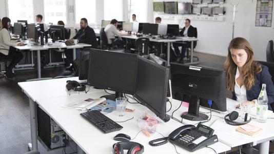 Mitarbeiter von Airmotion Media arbeiten an Schreibtischen mit Bildschirmen