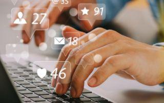 Hand auf Laptop-Tastatur, Symbole für Social-Media-Reaktionen